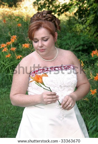 Beautiful bride on a Summer's day outside on a sunny day hold an orange day Lilly.  Taken in shadow. - stock photo