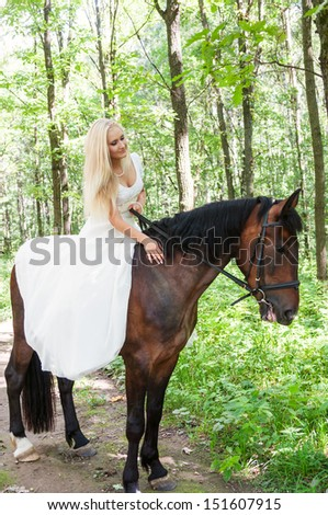 Beautiful bride on horseback in the forest