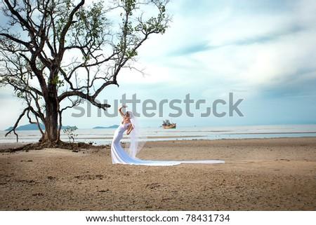beautiful bride on the beach in wedding dress - stock photo