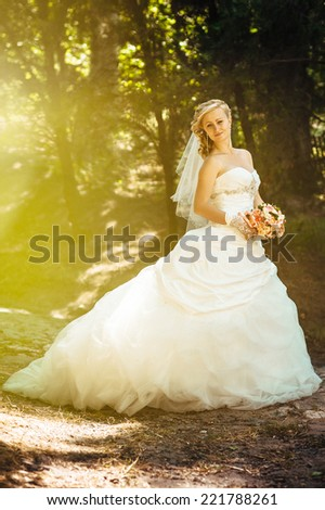 Beautiful bride outdoors. Bride holding wedding bouquet outside. Bride. Wedding hairstyle. A shot of a beautiful caucasian bride outdoor - stock photo