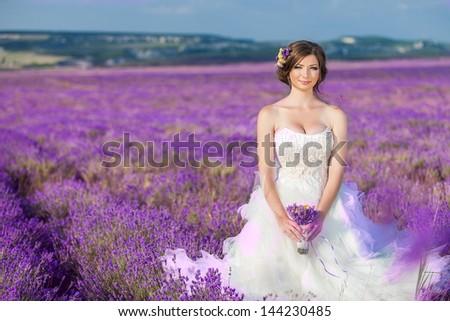 Beautiful bride posing at field of lavender - stock photo