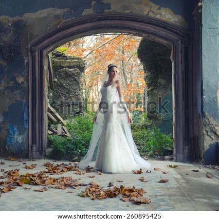 Beautiful bride posing in old ruined castle.