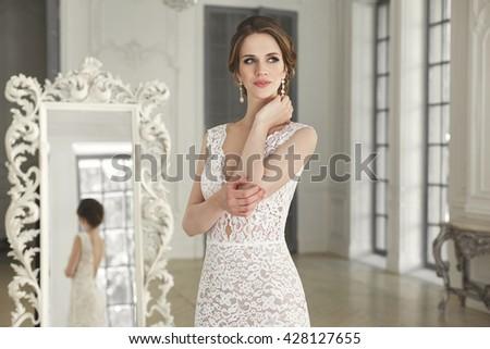 Beautiful bride posing in wedding dress in a white photo Studio. Mirror. Sofa. Bouquet. The door. Chandelier. - stock photo