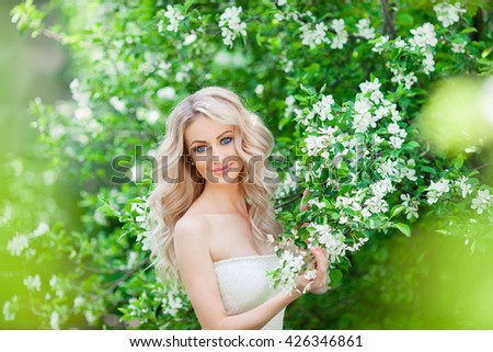 Beautiful bride posing near apple-tree in blossom