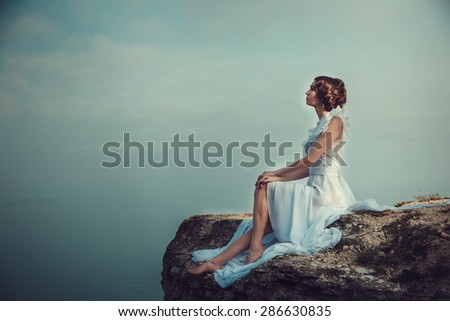 Beautiful bride posing on the coast with angelic dress. Bride in wedding dress stands on a cliff with a beautiful sea view from the top - stock photo