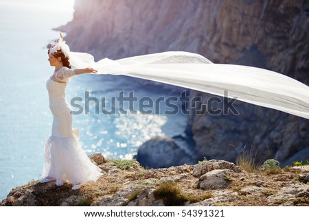 Beautiful bride posing over sea landscape - stock photo