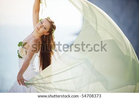 Beautiful bride posing over sea landscape - stock photo