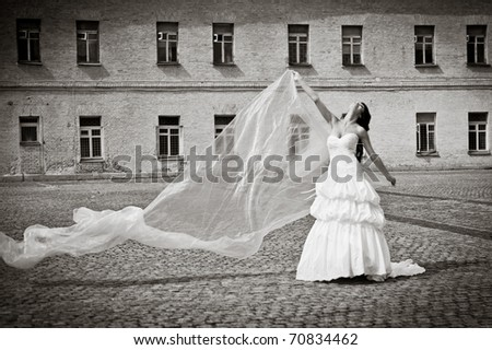 beautiful bride posing with long tulle - stock photo