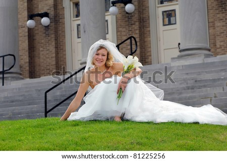 Beautiful bride relaxes on the grassy lawn in front of the church.  She is barefoot and holding her bouquet of calililies - stock photo