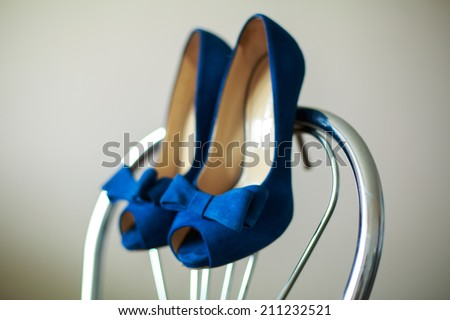 beautiful bride shoes   beautiful girl in shoes with high heels elegant pair of blue shoes with heels  shoes on a chair blue shoes with a gorgeous bow hanging on the back of a chair - stock photo