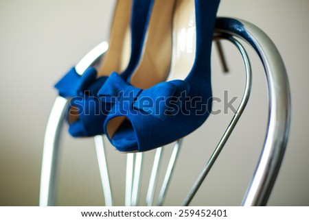 beautiful bride shoes   beautiful girl in shoes with high heels elegant pair of blue shoes with heels  blue shoes on a chair - stock photo