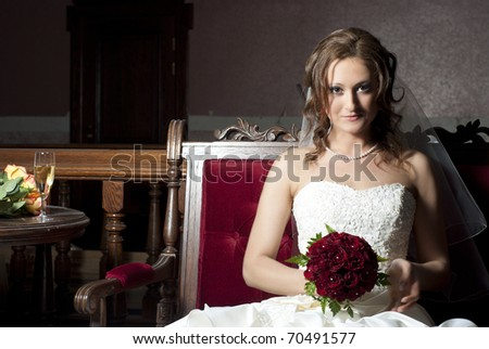 Beautiful bride sitting on a sofa - stock photo