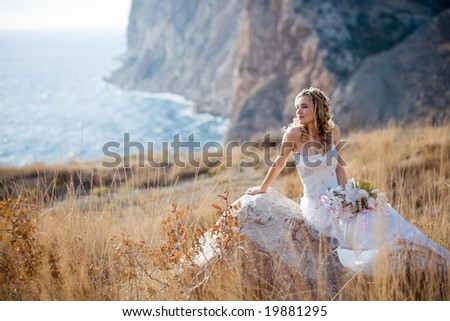 Beautiful bride sitting on stone at field over mountains and sea coast landscape - stock photo