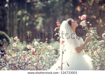 Beautiful Bride smell the roses. Wedding theme with flowers