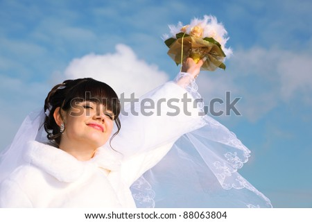 beautiful bride smiles, closed her eyes and raised her hand with bouquet of roses at winter outdoors - stock photo