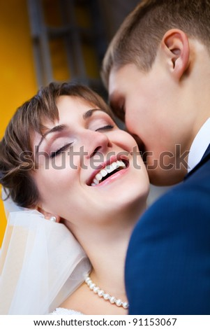 Beautiful bride smiling while groom telling her something - stock photo