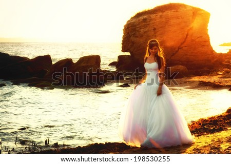 Beautiful bride walking along the seaside at sunset - stock photo