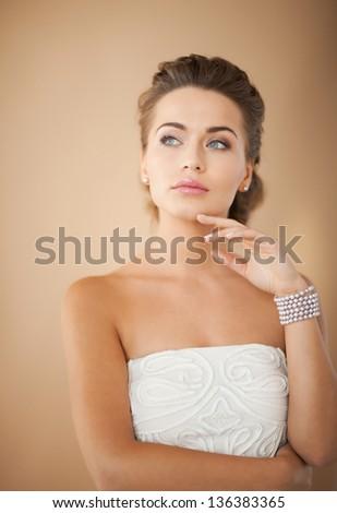 beautiful bride wearing pearl earrings and bracelet - stock photo
