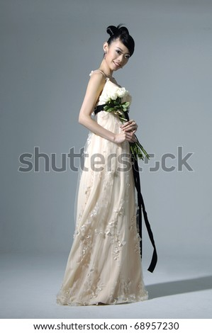 beautiful bride wearing wedding dress with a bouquet of flowers - stock photo