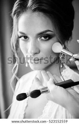Beautiful bride wedding makeup and hair-style. Stylist makes makeup bride on wedding day. portrait of young bride at wedding day