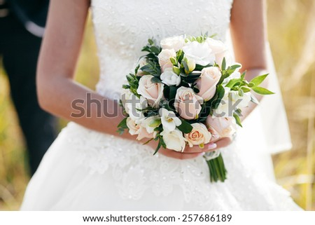 beautiful bride with a bouquet of delicate flowers - stock photo
