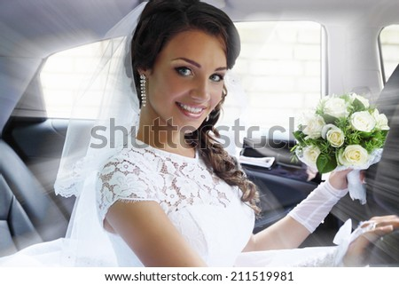 beautiful bride with a bouquet of roses sitting in the car - stock photo