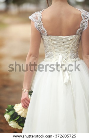 Beautiful bride with a bouquet standing back - stock photo