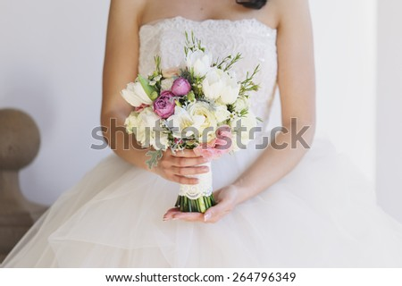 Beautiful bride with a stunning dress posing on her wedding day - stock photo