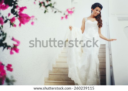 Beautiful bride with black hair down the stairs to the groom on the island of Santorini - stock photo