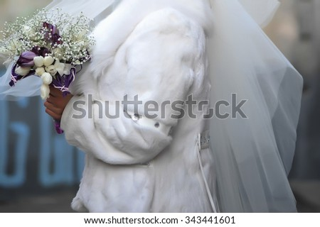 Beautiful bride with bouquet before wedding ceremony. Winter. - stock photo