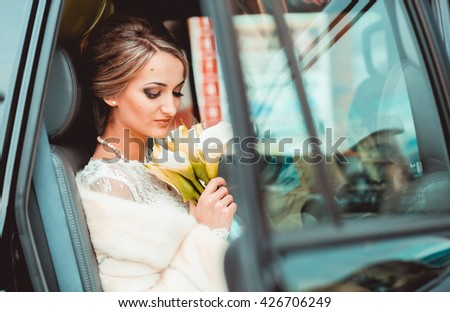 Beautiful bride with bouquet of flowers in the car