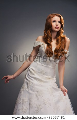 beautiful bride with curly red hair in wedding dress