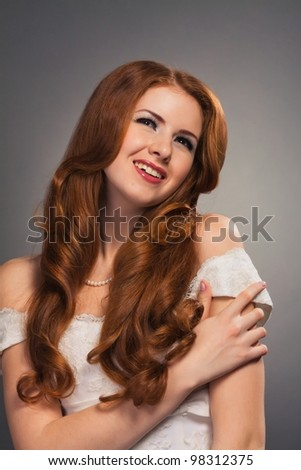beautiful bride with curly red hair in wedding dress - stock photo