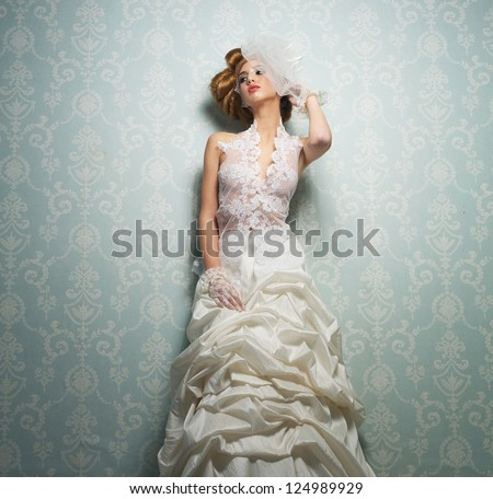 Beautiful bride with elegant white wedding dress with hand to head - stock photo