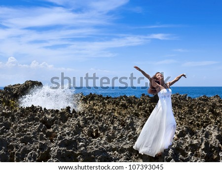 Beautiful bride with eyes closed standing on reefs near the ocean - stock photo