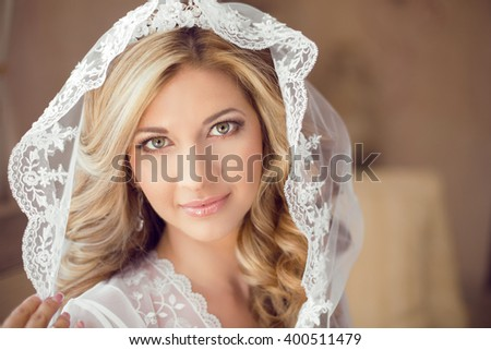 Beautiful bride with fashion wedding hairstyle in white veil. Closeup portrait of young gorgeous bride. Makeup.  - stock photo