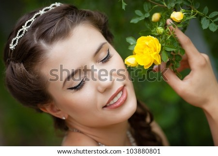 Beautiful bride with rose flower near face - stock photo