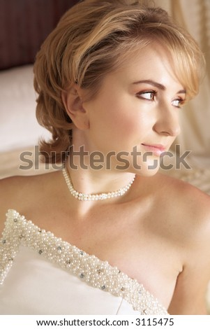 Beautiful bride with short blond hair in pearl beaded dress and soft make-up - stock photo