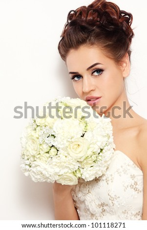 Beautiful bride with stylish make-up and hairdo holding bouquet in her hand, over white wall - stock photo