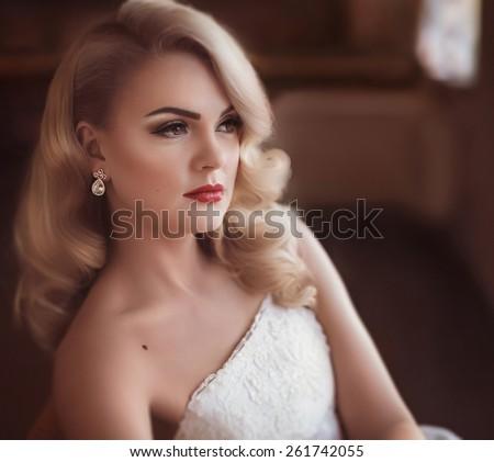 Beautiful bride with stylish make-up in white dress - stock photo