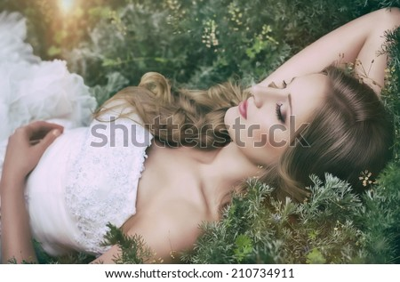 Beautiful bride with stylish make-up in white dress in spring garden - stock photo
