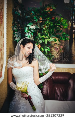 Beautiful bride with wedding bouquet of flowers, attractive woman in wedding dress. Happy newlywed woman. Bride with wedding makeup and hairstyle. Smiling bride. Wedding day. Gorgeous bride. Marriage. - stock photo