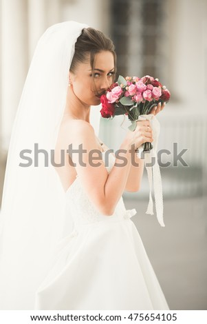 Beautiful bride with wedding bouquet posing in old city