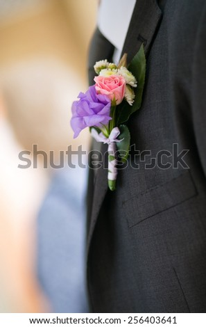 Beautiful bright boutonniere on a gray jacket groom, wedding