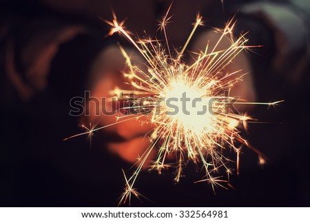 beautiful bright celebratory sparkler in woman hands - stock photo