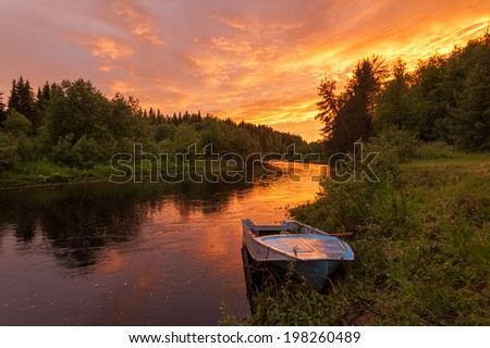 Beautiful bright dramatic sunset over river with forest along riverside and boat in foreground. Arkhangelsky region, Russia.  - stock photo