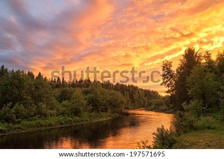 Beautiful bright dramatic sunset over river with forest along riverside. Arkhangelsky region, Russia.  - stock photo