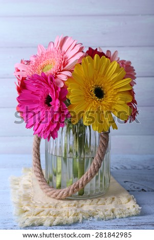 Beautiful bright gerberas in vase on wooden background - stock photo