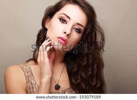 Beautiful bright makeup woman with long hair touching the face - stock photo