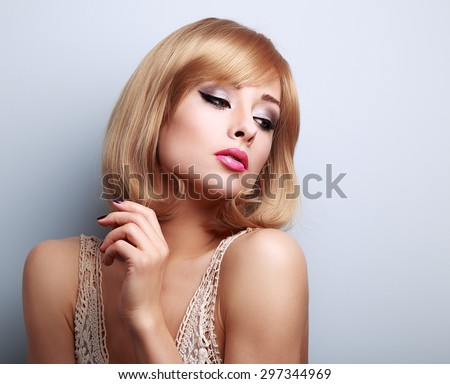 Beautiful bright makeup woman with short blonde hair style looking down on blue background with empty copy space - stock photo